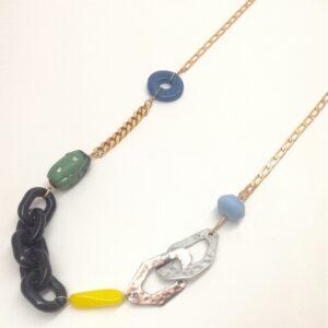 Collier long avec différentes chaînes et avec des perles aux matières et formes diverses.