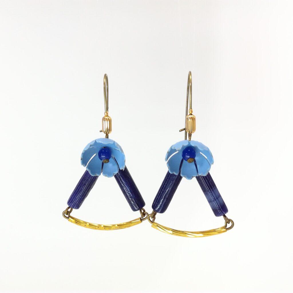 Boucles d'oreilles réalisées avec une petite fleur en plastique bleu charette  des perles de verre bleues ainsi qu'un tube en laiton brut texturé.