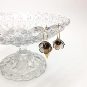 Créole de 2cm de diamètre dorée à l'or fin avec une petite corolle en plastique fumé  perle ronde noire. Estampes plume et fleur à 4 feuilles dorées à l'or fin.
