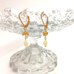 D'anciennes perles de chapelet blanc crème montées sur des petites flèches entremêlées et des dormeuses dorées à l'or fin.