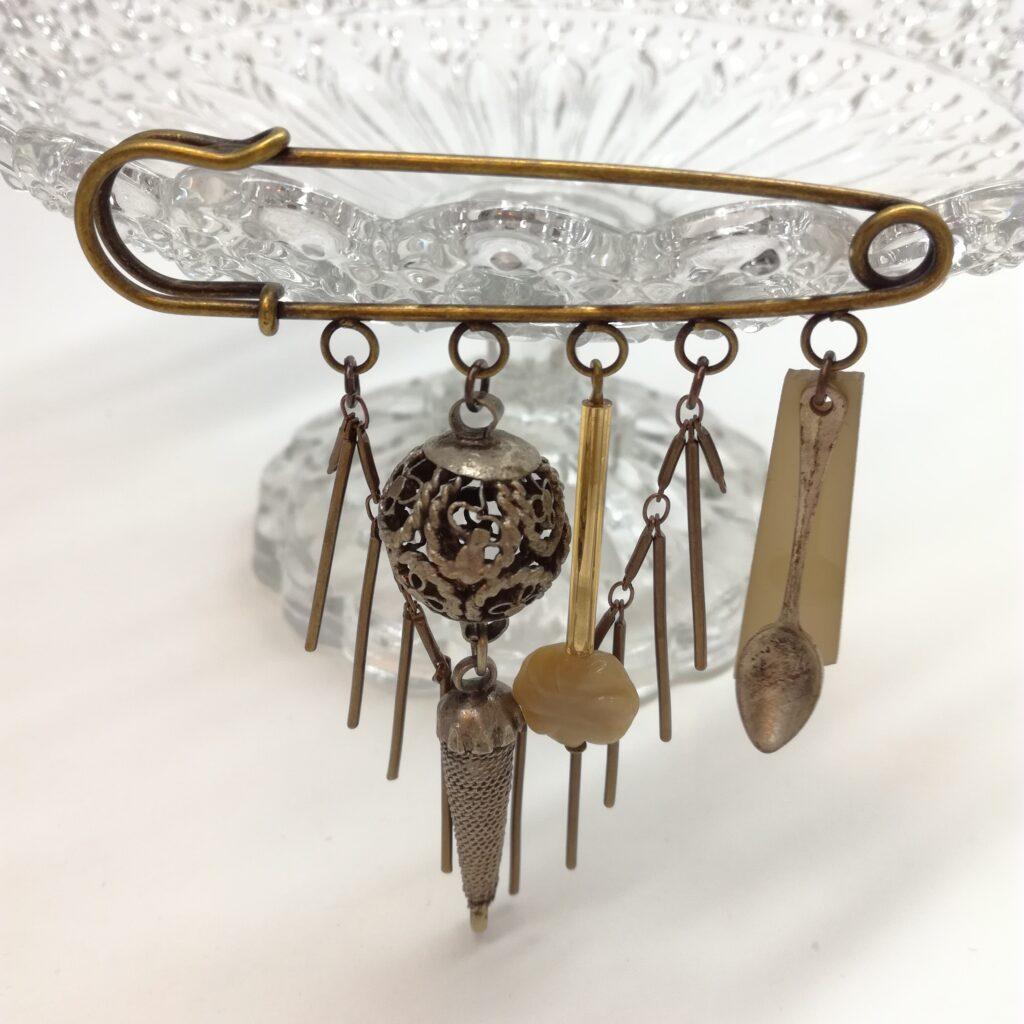 Broche de 8 cm constituée de petits trésors et d'une chaîne bâton.