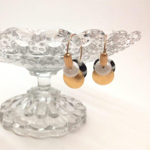 Créoles dorées à l'or fin de 20mm de diamètre. Perle de verre bicolore blanche et noire de fabrication indienne des années 1970 en forme de disque. Estampe ronde bombée inspirée de la période Art Déco. Petite perle de verre blanche nacrée et perle vintage métallique tubulaire striée.