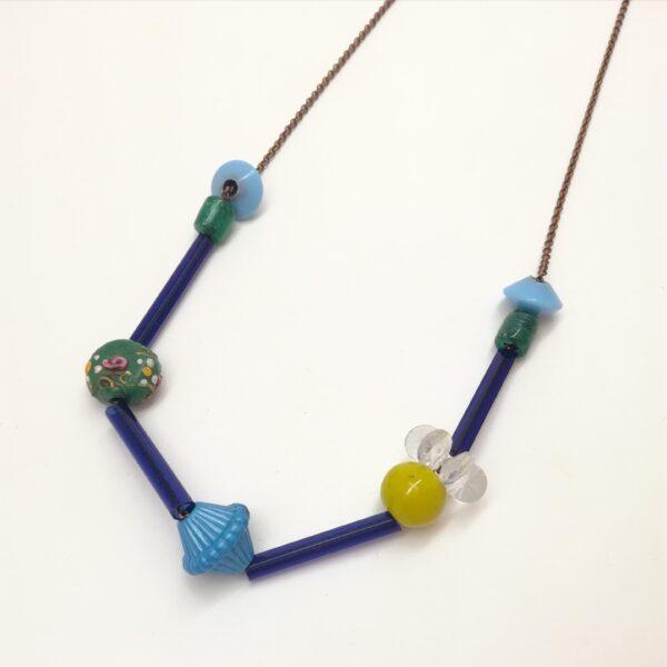 Collier de 76cm de longueur composé de tubes de verres et de perles de formes diverses et variées en couleurs  formes et matières. Couleur dominante : bleu.