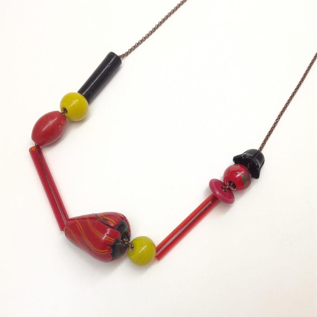 Collier de 76cm de longueur composé de tubes de verres et de perles de formes diverses et variées en couleurs  formes et matières. Couleur dominante : rouge.