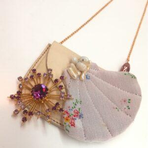 """Sautoir composé d'un ancien étui à chapelet  d'une broche dite """"atomique"""" violette  d'une ancienne perle de verre torsadé de couleur cuivre et d'un coquillage textile réalisé à partir de tissu chiné  rebrodé de perles de varre nacrées. La pochette est encore fonctionnelle de manière à pouvoir porter tout message contre votre coeur."""