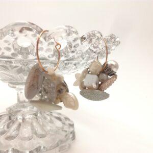 Créoles asymétriques dorées à l'or fin de diamètre 2cm.  Diverses éléments compose chaque boucles d'oreilles dans les tons de blanc et transparent : sequins  perles de verre  boutons anciens.