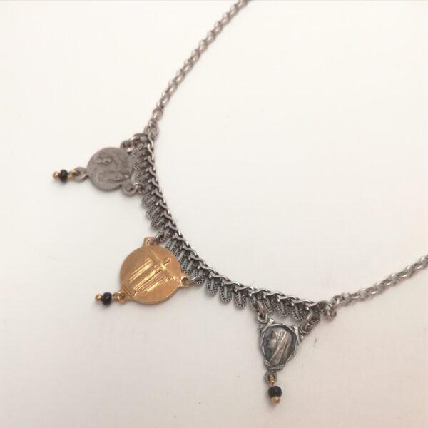 Collier en métal argenté composé de 2 chaînes différentes et de 3 anciens coeurs de chapelets au bout desquels j'ai ajouté une petite perle de rocaille noire.