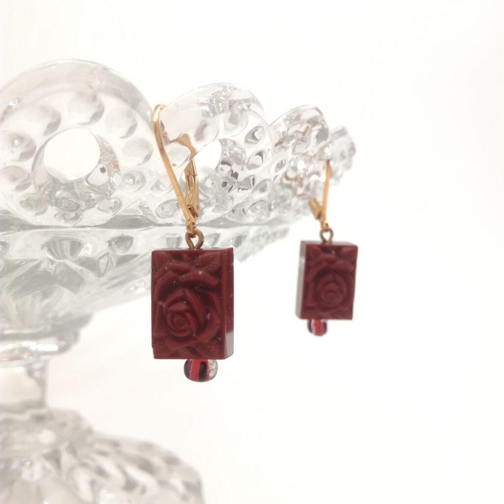 Dormeuses dorées à l'or fin composées d'une perle moulée durant la période Art déco de couleur marron avec perle ancienne rayée orange et noire. Cette perle représente une rose avec ses feuilles.