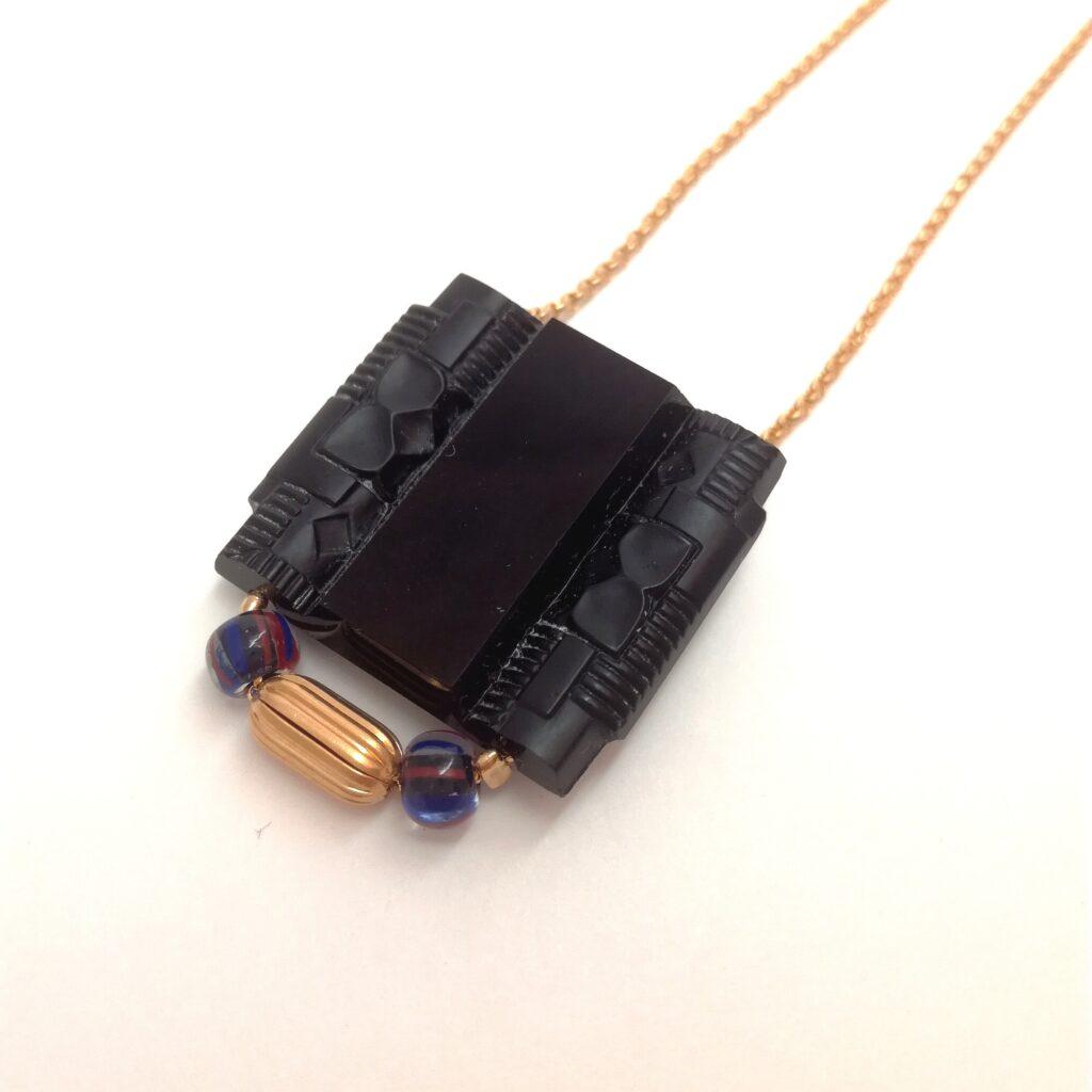 Collier avec fine chaîne en laiton doré à l'or fin composée d'une perle datant de la période Art Déco  de 2 perles de verre anciennes de couleur bleu marine et striée de orange/rouge et d'une perle métallique vintage allongée striée en laiton doré à l'or fin.