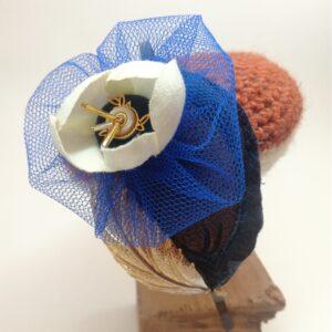 Serre-tête/bibi en métal noir composé d'un élément textile reprenant un élément d'une plume de paon  d'une fleur de résille bleu électrique à l'intérieur de laquelle se trouve une fleur articielle aux pétales blancs  une estampe métalliqe dorée filigranée et diverses perles anciennes.