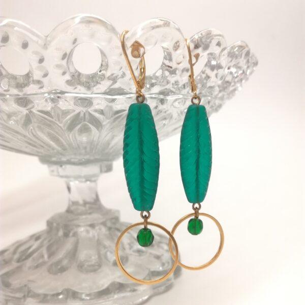 Dormeuses avec ancienne perle de verre vert émeraude et petite perle facettée en verre vert translucide au centre d'un cercle de laiton. Tous les éléments métalliques sont en laiton doré à l'or fin.