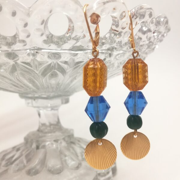 Dormeuses Totem avec un assemblage de perles aux formes et couleurs variées et estampe de style Art Déco. Tous les éléments métalliques sont en laiton doré à l'or fin.