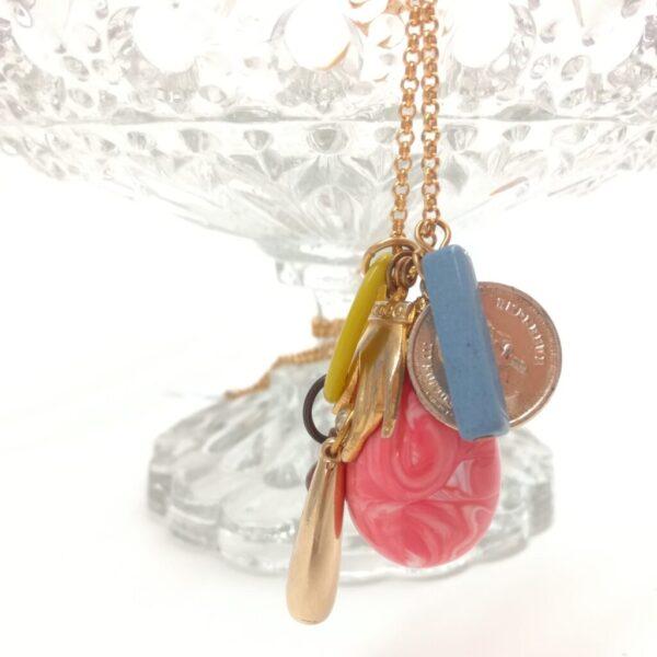 Collier avec accumulation de petits trésors dans le tons doré  argenté  jaune  bleu et rose.