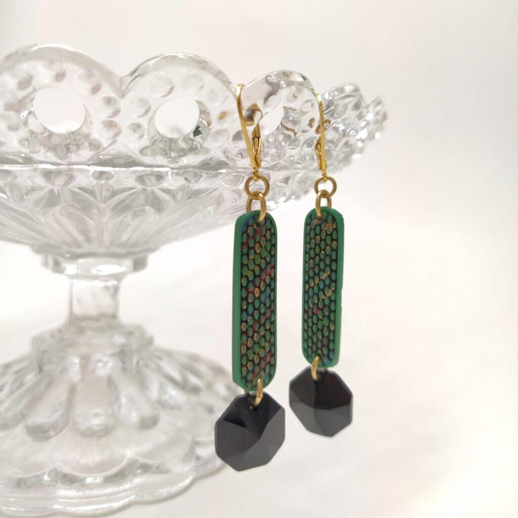 Dormeuse en laiton doré à l'or fin constitué des pates de verre antique verte émaillées en rouge  noir et or et d'une perle de cristal de swarovsky facettée noire.