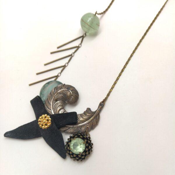 Sautoir aux chaînes en laiton bronze composé d'un bouton  d'une perle  d'une ancienne boucle d'oreille dans un ton vert d'eau  d'un petit noeud en daim noir et d'une broche argentée en forme de plume.