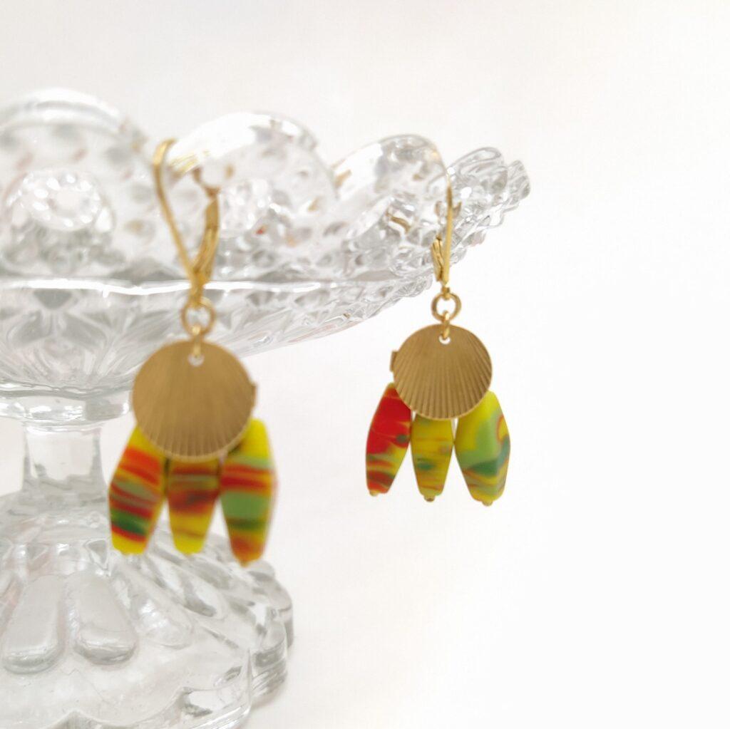 Dormeuses en laiton doré à l'or fin composées d'uns estampe de style Art Déco et de 3 perles de Briare anciennes oblongues de couleur dominante jaune avec traces de rouge et de vert. Ces perles sont très lumineuses.