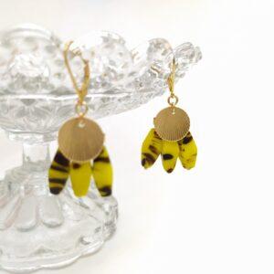 Dormeuses en laiton doré à l'or fin composées d'uns estampe de style Art Déco et de 3 perles de Briare anciennes oblongues de couleur dominante jaune avec traces de marron lui conférant un aspect léopard. Ces perles sont très lumineuses.