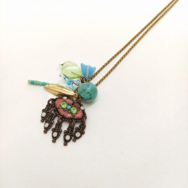 Collier avec accumulation de petits trésors dans le tons turquoise  bleu clair  vert  blanc et rose.