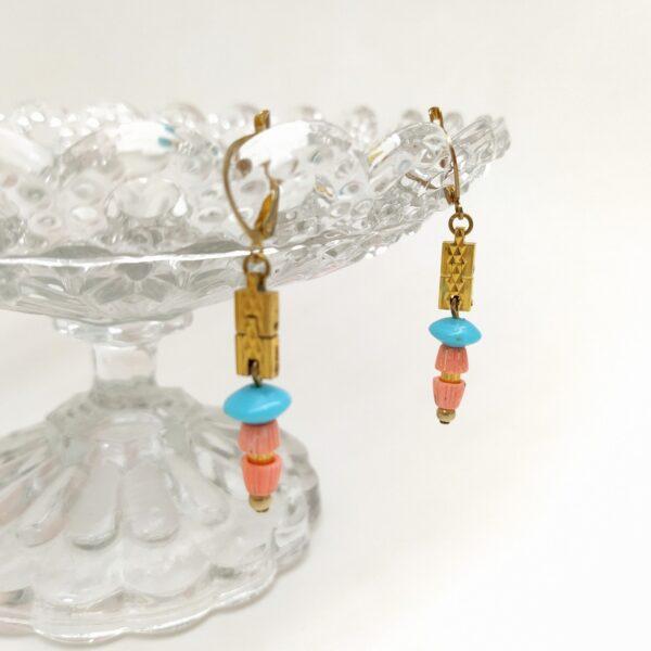 Dormeuses en laiton composées d'éléments de bracelets de montre anciens au bout desqueles sont suspendus diverses perles vintages dans les ton rose saumon et bleu turquoise.