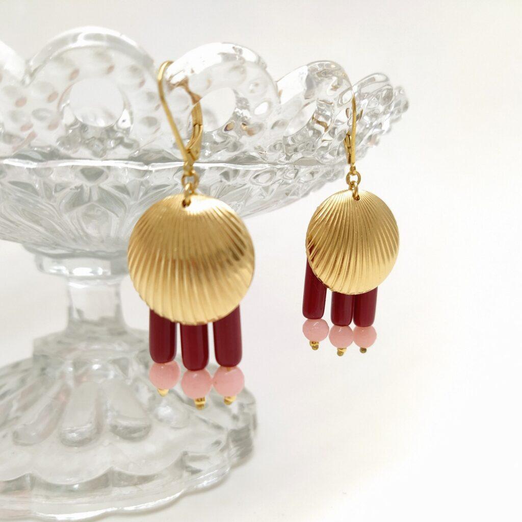 Dormeuses en laiton doré à l'or fin composées de perles de verres longues et rondes surmontées d'une estampe en laiton doré d'inspiration Art Déco.