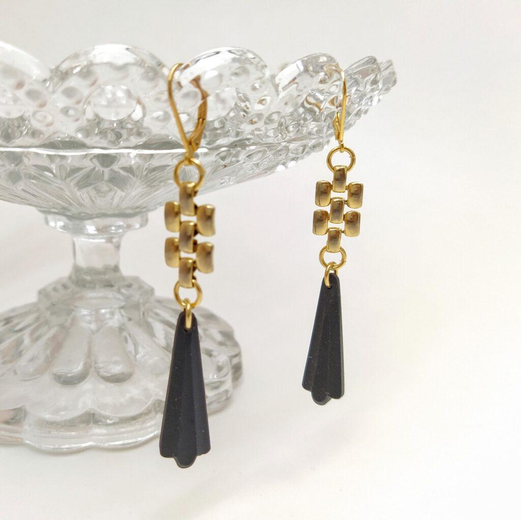 Dormeuses en laiton doré à l'or fin composée d'antiques perles de verre mat noires réalisées durant la période Art Déco montées sur une chaîne de collier typique des années 1980.