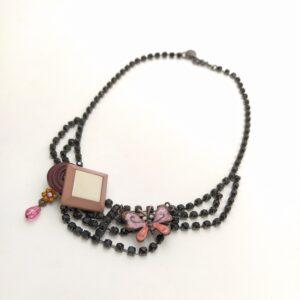Collier bucilique reprenant un collier strassé en noir de style baroque sur lequel est fixé 2 boutons aux formes géométriques  un papillon ainsi qu'une fleur métalliques émaillés.