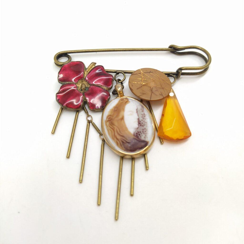 Broche épingle en laiton bronze composée d'une boucle d'oreille clip émaillée en rouge  d'un camée faisant penser à Peau D'Âne  d'un bouton beige pailleté  d'un eprle facettée pendante ambrée et du'ne chaîne bâton en laiton bronze.