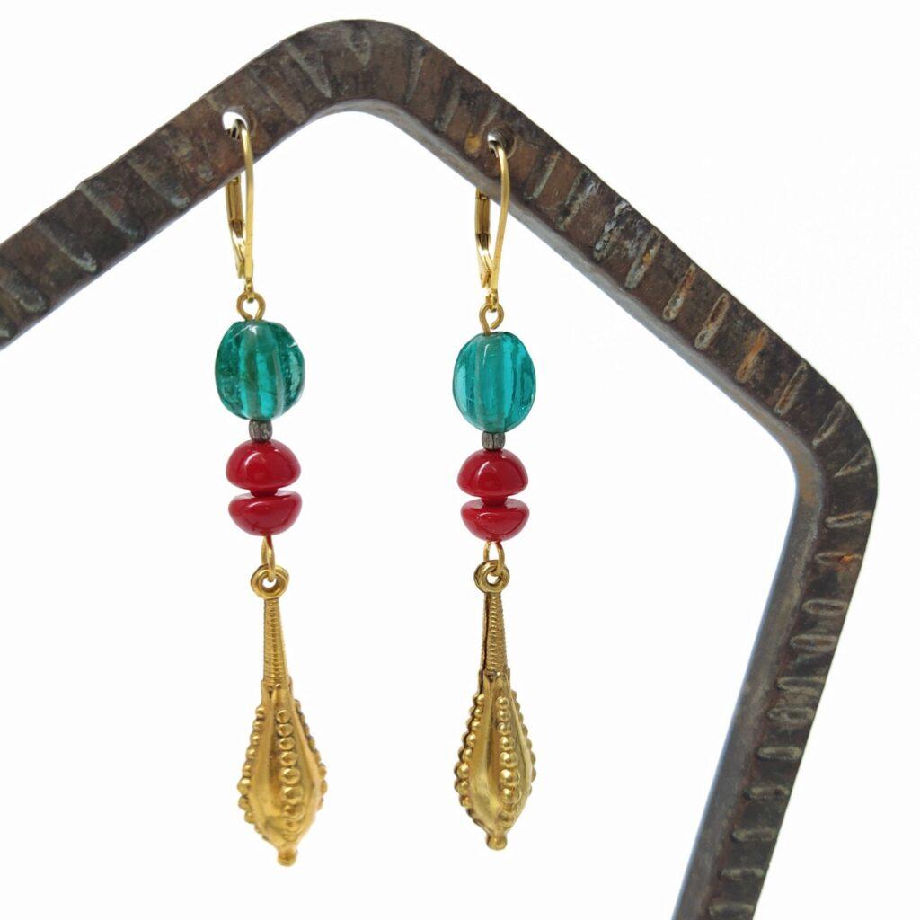 Dormeuses en laiton doré à l'or fin composées de diverses perles de verre et d'antiques estampes dorées.