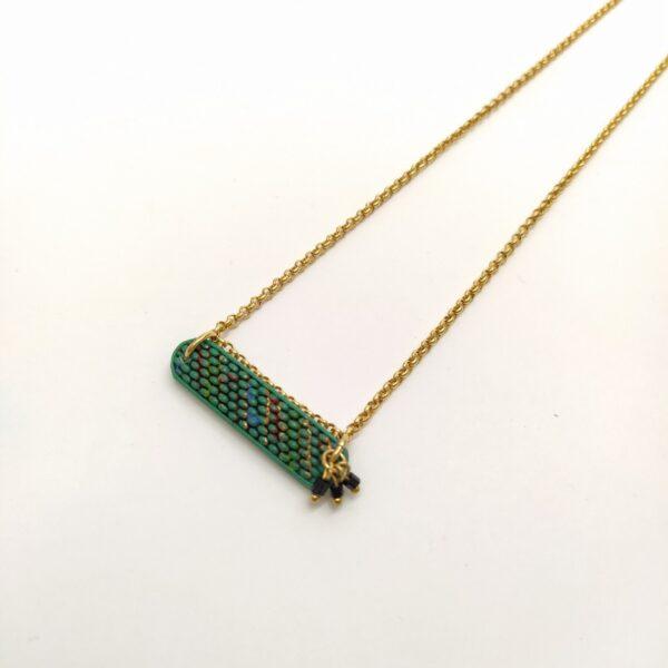 Collier court composé d'une chaîne jaseron en laiton doré à l'or fin  d'une pâte de verre Art Déco verte émaillée en rouge  noir et or (3cmx0 8cm). Des petites perles de rocailles sont fixées sur un côté du pendentif ainsi qu'au niveau de la chaîne de réglage.