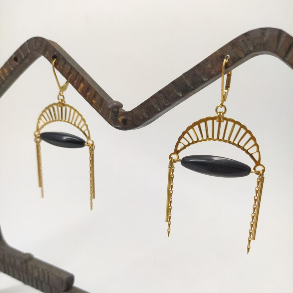 Dormeuses en laiton doré à l'or fin composé d'une estampe en forme de lune  d'une perle de verre ancienne oblongue noire et d'autres petites chaînes dorées.