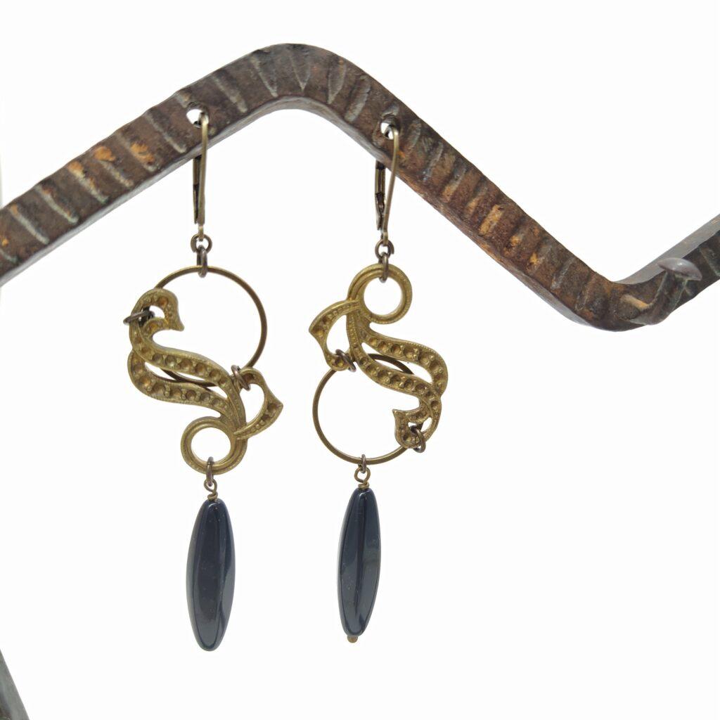 Dormeuses asymétriques en laiton bronze composées d'un petit cercle de laiton complété d'une estampe Art Nouveau ainsi que d'une perle de verre oblongue noire.