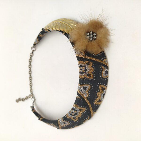 Torque métallique recouvert d'un ruban noir  doré et argenté sur lequel est fixé un bouton de vison strassé ainsi qu'une ancienne boucle d'oreille clip en forme de feuille.