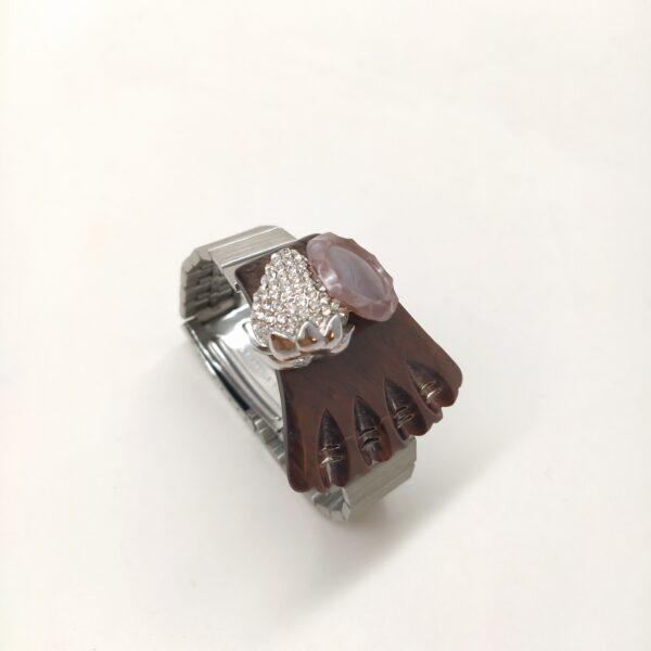 Manchette composée d'un bracelet montre argenté composé d'un élément de boucle de ceinture en bakélite marron  une fraise argentée et strassée ainsi que d'un bouton parme nacré.
