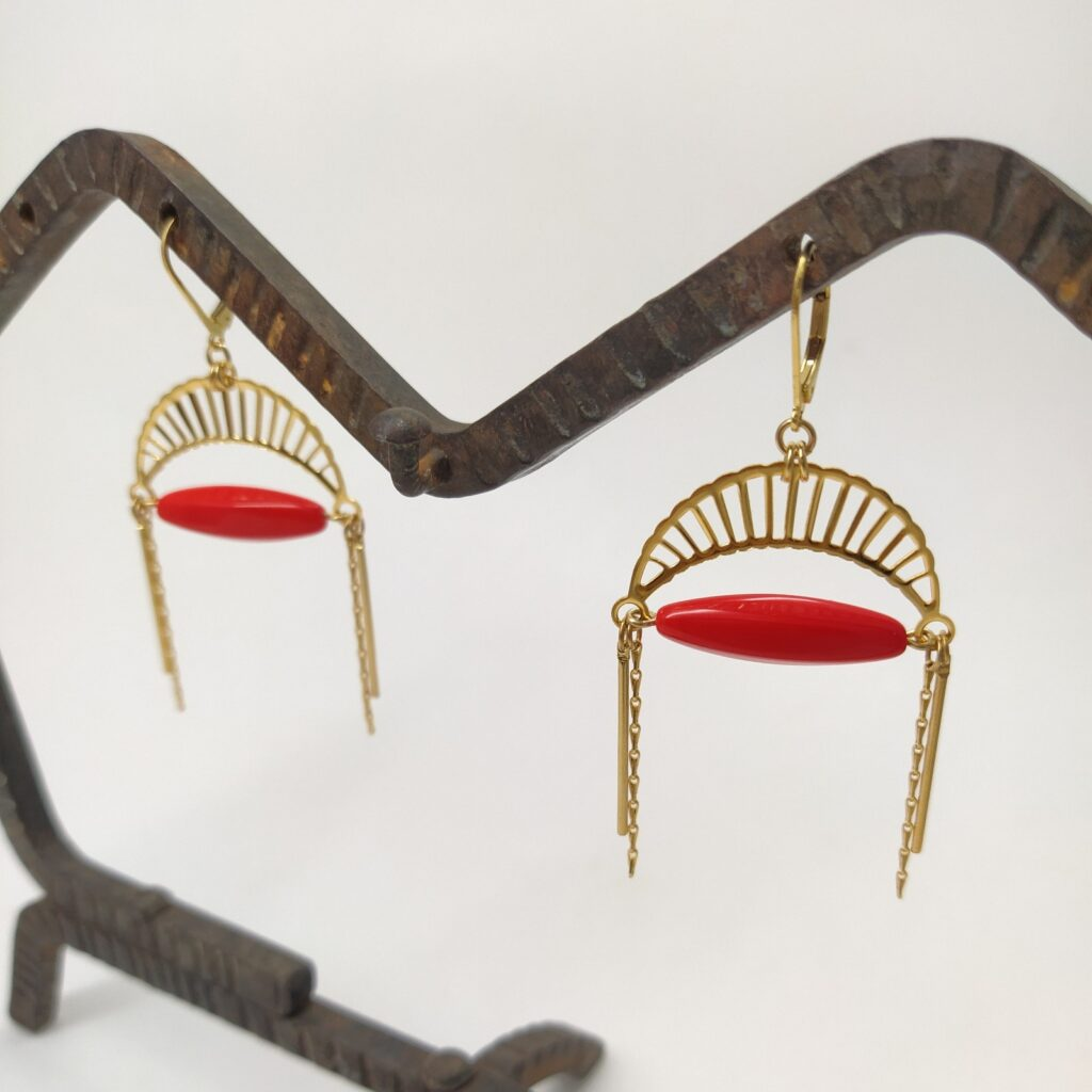 Dormeuses en laiton doré à l'or fin composé d'une estampe en forme de lune  d'une perle de verre ancienne oblongue rouge orangé très lumineuses et d'autres petites chaînes dorées.