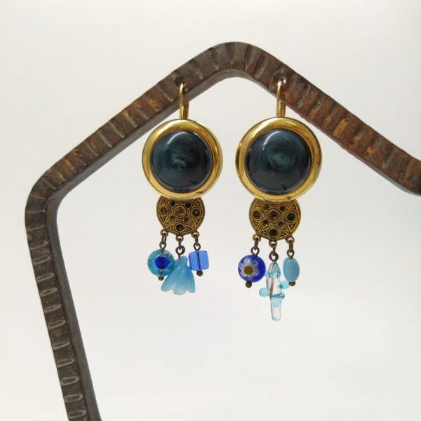 Dormeuses asymétriques en laiton doré à l'or fin composées d'anciennes boucles d'oreille Art Déco  de boutons et de perles de verre variées dans les tons de bleu. Murano  swarovsky et années 1960.