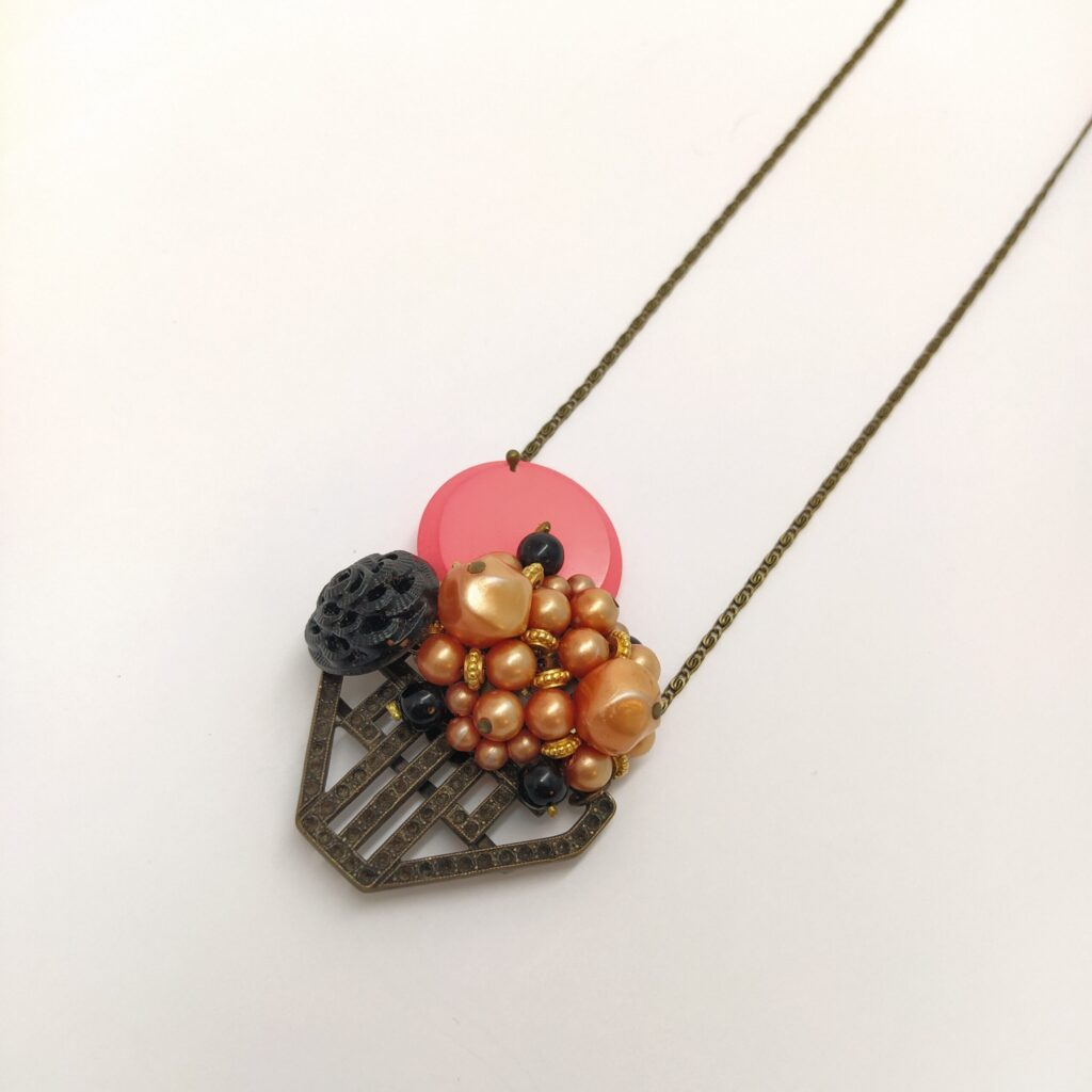 Sautoir en laiton bronze composé d'un élément de boucle de ceinture Art Déco  d'un clip vintage composé de perles nacrées orangées  d'un bouton de verre des années 1930 et d'un bouton des années 1980 rose fluo.