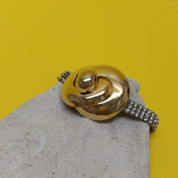 Bracelet extensible composé de strass et de chaînes boule argentée surmonté d'un clip vintage doré des années 1980.