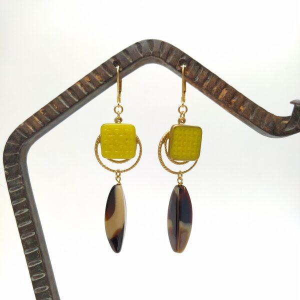 Dormeuses en laiton doré à l'or fin composé d'une estampe dorée  d'un bouton de verre Art Déco et d'une perle de verre antique à l'apparence d'écaille de tortue.