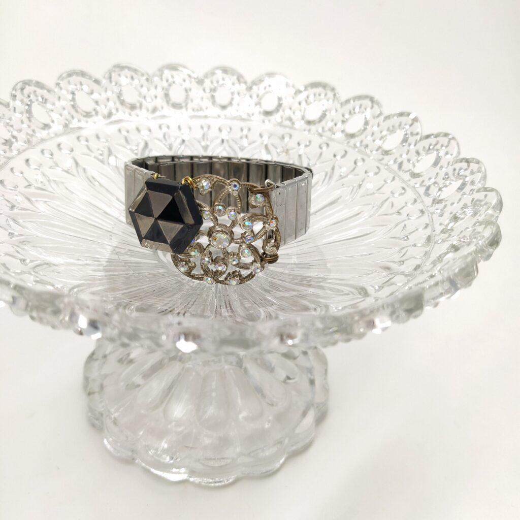 Bracelet montre argenté réglable (largeur 1 8cm) revisité avec une perle de verre hexagonale des années 1930 noir et argentée et une ancienne broche argentée strassée.