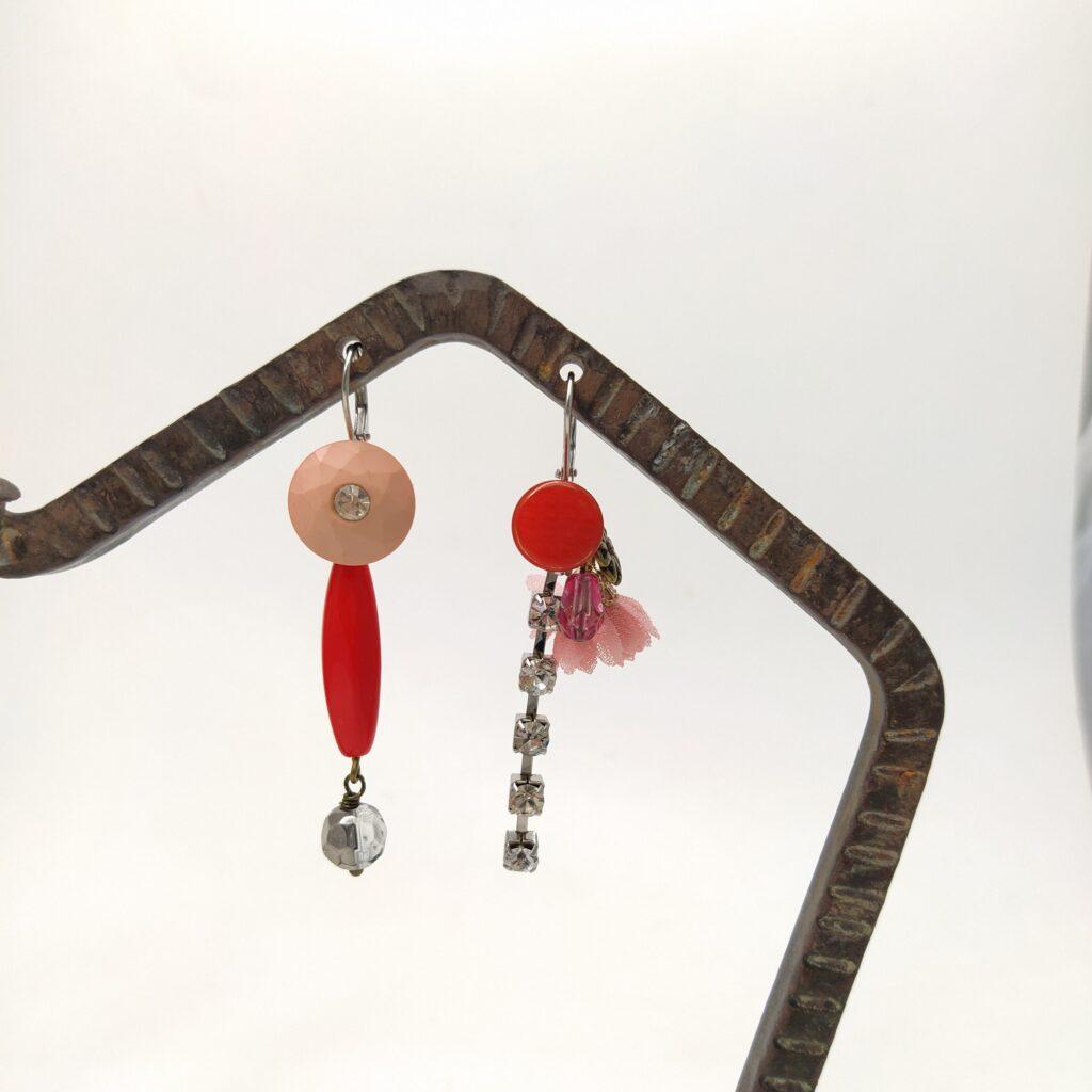 Dormeuses argentées asymétriques composées de boutons d'époques variées  de chaîne strassée  de perles de verre et d'autres éléments métallique et textile.