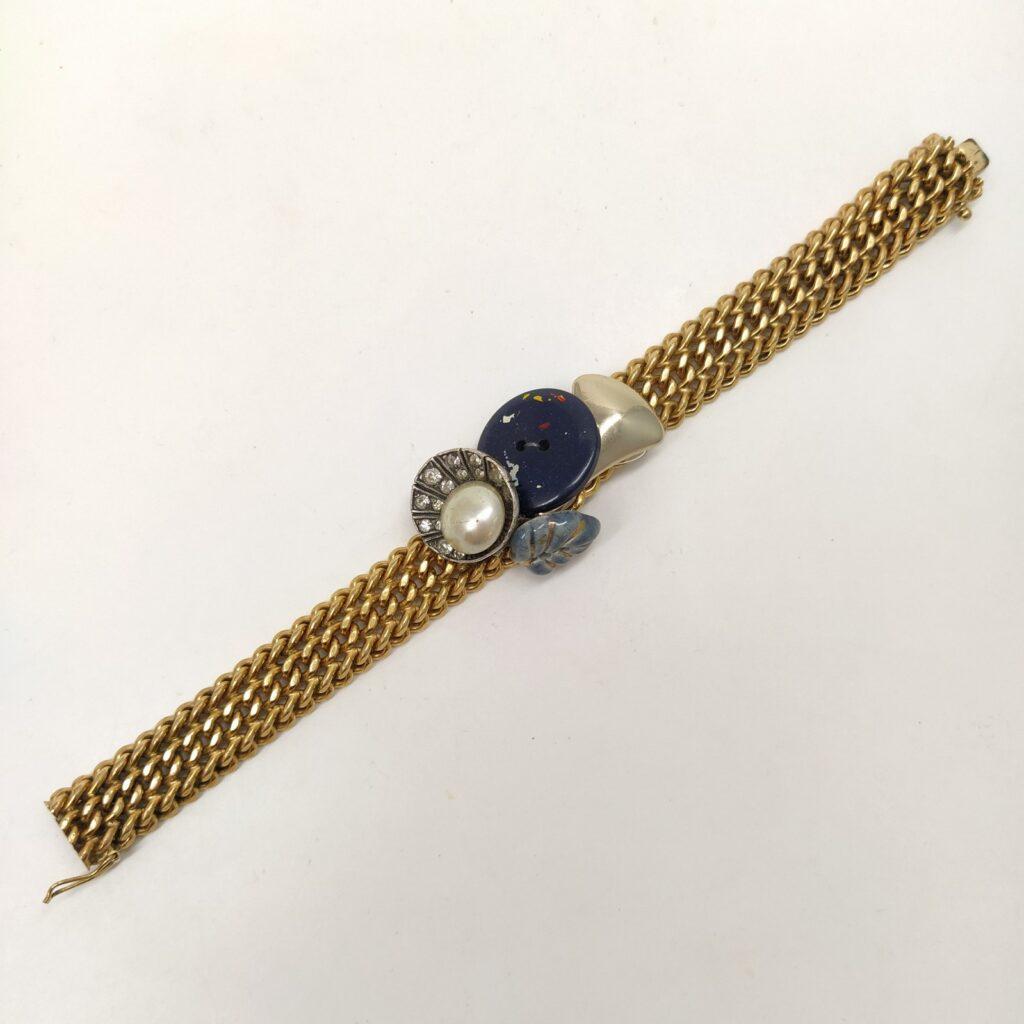 Bracelet en maille plaqué or composé d'une ancienne boucle d'oreille clip style Art Déco  un bouton de céramique émaillé gris et or  un bouton plastique avec éclats de peinture  un élément de bracelet en métal doré.