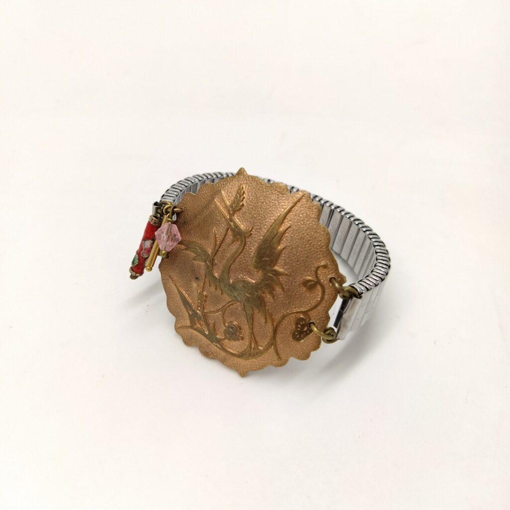 Bracelet montre réglable argenté de largeur 1cm avec ancienne broche cuivrée repésentant une grue ainsi qu'une perle de verre facetté rose  un tube de métal doré et une perle métallique cloisonnée.