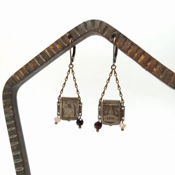 Dormeuses  asymétriques en laiton bronze élaborées à partir d'éléments en métal argenté représentant des monuments parisiens au bout desquels sont suspensdues de perles de verre facettées.