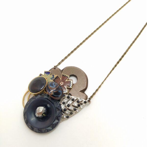 Sautoir avec chaîne en laiton bronze composé d'un élément de boucle de ceinture brun en bakélite sur lequel sont fixées  boutons  perles et pendentif et ancienne boucle d'oreille.