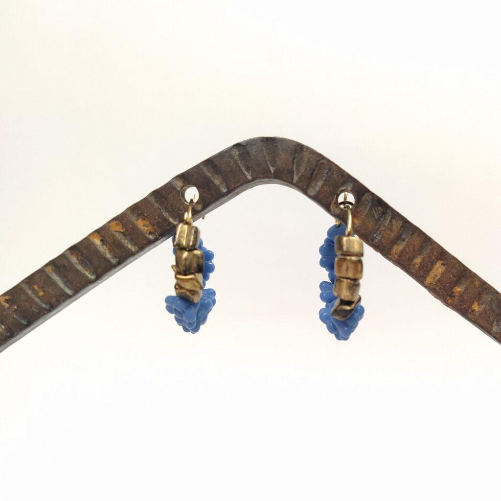 Créoles en laiton doré à l'or fin de diamètre 2cm composées de perles de verre bleu pervenche en forme de fleurs des années 1980 et de perles de verre bronze des années 1960.