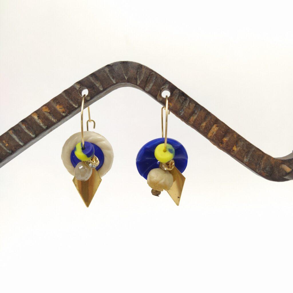 Créoles asymétriques en laiton diré à l'or fin composées de boutons  de perles vintage de verre et d'ivoire et d'estampes dorées en forme de losange.