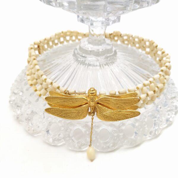 Tour de cou de 36 5 cm de long composés de perles d'ivoires sur lequel j'ai ajouté une ancienne broche libellule. La pauvre  ayant perdu sa queue  je lui en ai rajouté une avec une perle d'ivoire au bout. Pour le voir porté  n'hésitez pas à me contacter par téléphone.