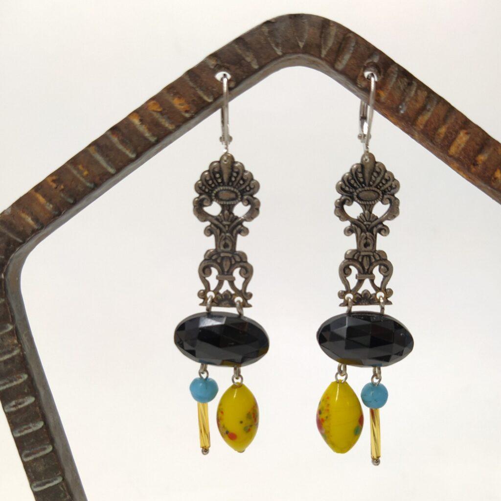 Dormeuses en laiton argenté composées d'estampes avec un petit côté aztèque  de perles de jais facettées de forme ovale et d'autres perles de vere chinées.