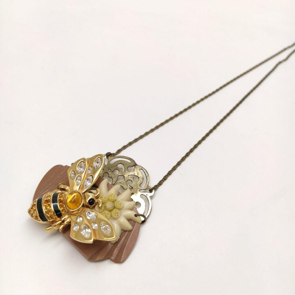 Sautoir composé d'une boucle d'oreille dorée patinée par le temps sur laquelle sont fixées une boucle de ceinture en bakélite  une broche fleur edelweiss et une broche abeille flamboyante.