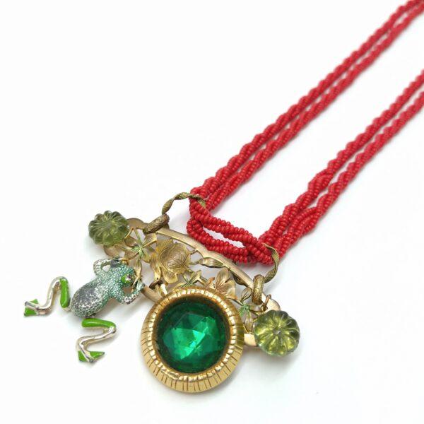 Collier composé d'un collier de perles de rocaille rouge associé à une composition comprenant une ancienne broche  des cabochons de fleur en verre  une broche grenouille articulée et d'un clip d'oreille vintage.